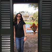 Photo of Liz Carter standing in outdoor doorway in front of building and reflecting pool